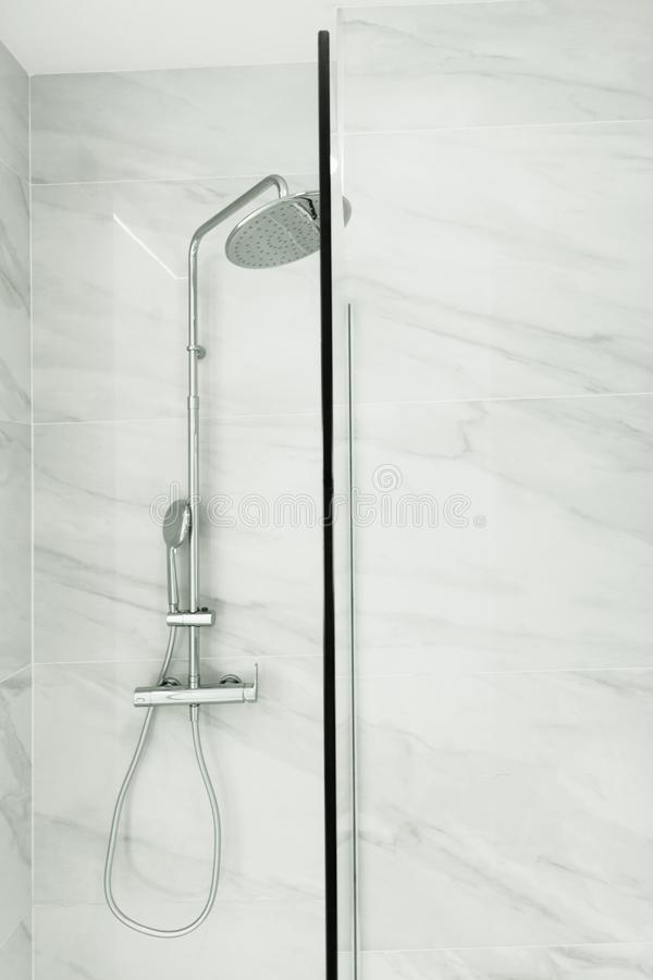 Fragment of bathroom interior with tempered safety glass enclosure with shower fittings head hanging on tiled wall. Modern minimal royalty free stock photo