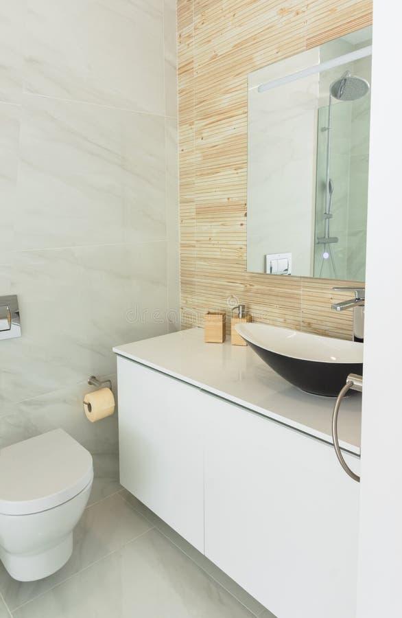 Fragment of bathroom interior wash basin unit cabinet mirror toilette bowl. Modern minimalist style practical design materials. Accessories royalty free stock photo