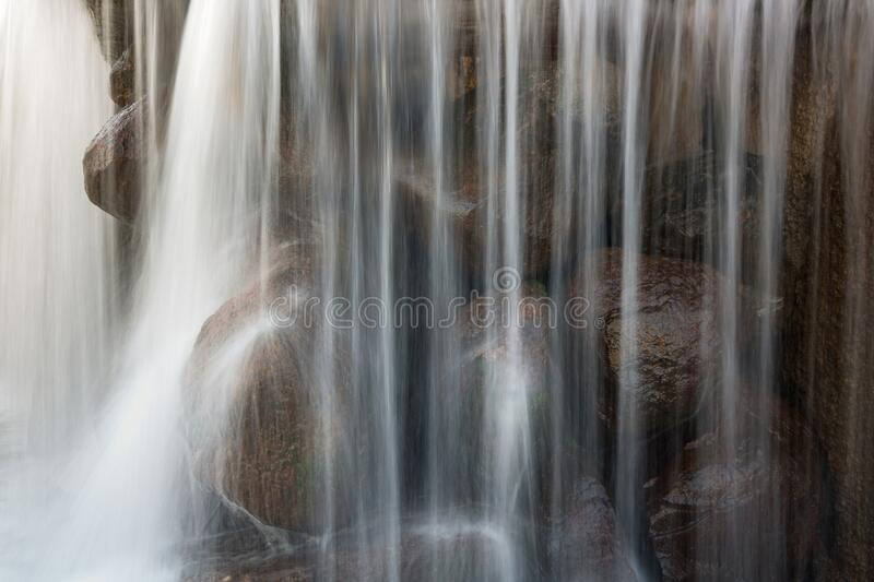 Fragment of a beautiful waterfall with large stones with vertical blurry streams and splashes. close-up side view. Fragment of a beautiful waterfall with large stock photo