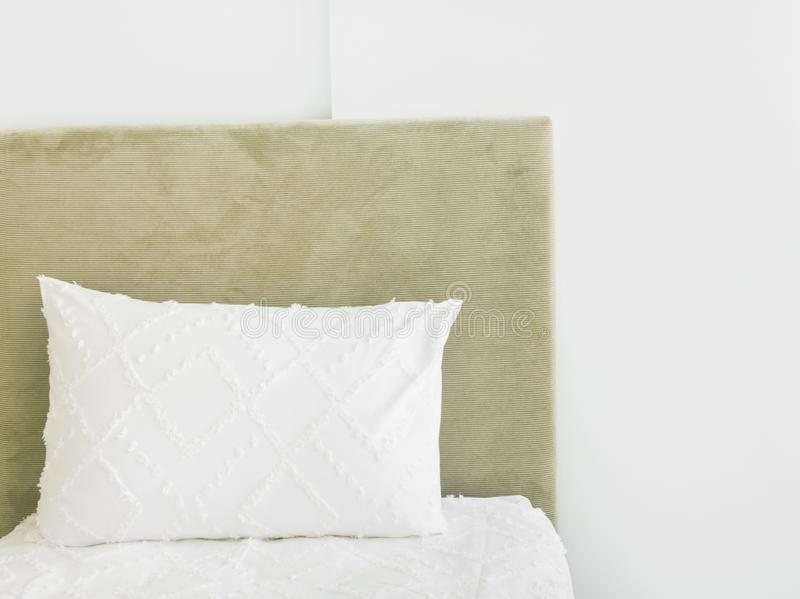 Fragment of bedroom interior in luxurious hotel bed with upholstered velour bedhead board white pillow pure cotton bed linen wall. Scandinavian minimalist stock images