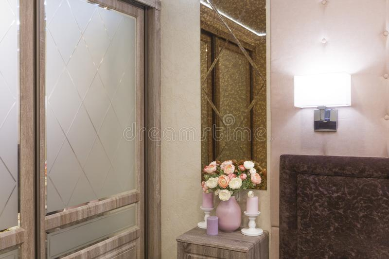 Fragment of a bedroom in pink and brown colors, decorated with mirrors royalty free stock image