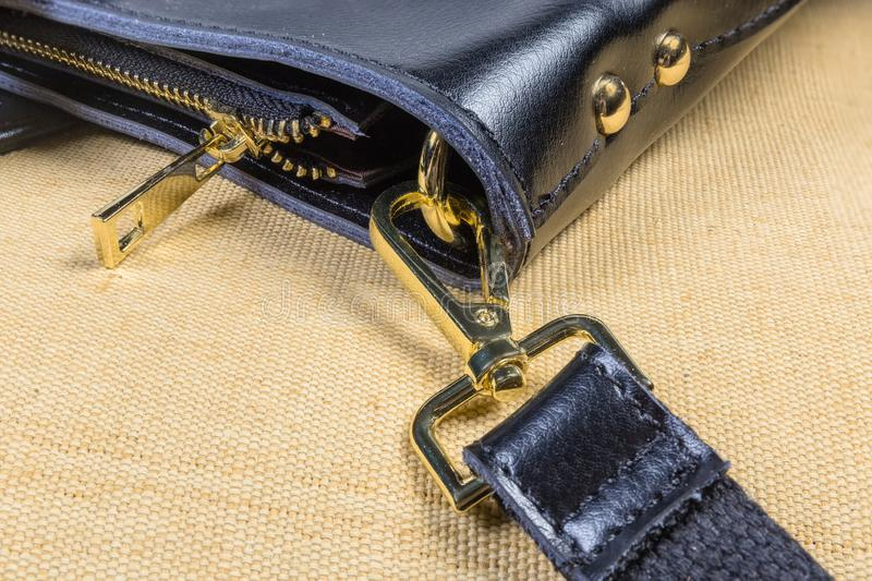 Fragment of black handbag with some yellow metal bag accessories. Fragment of the black leather handbag with shoulder strap. Some fashion yellow metal bag royalty free stock photo