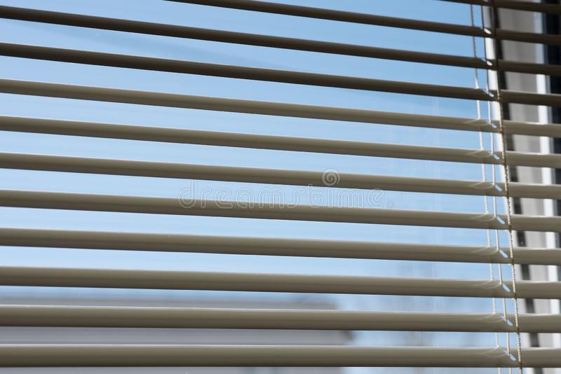 Fragment of blinds on the window. You can see the sky through the blinds. Sun blinds hanging on the window stock images