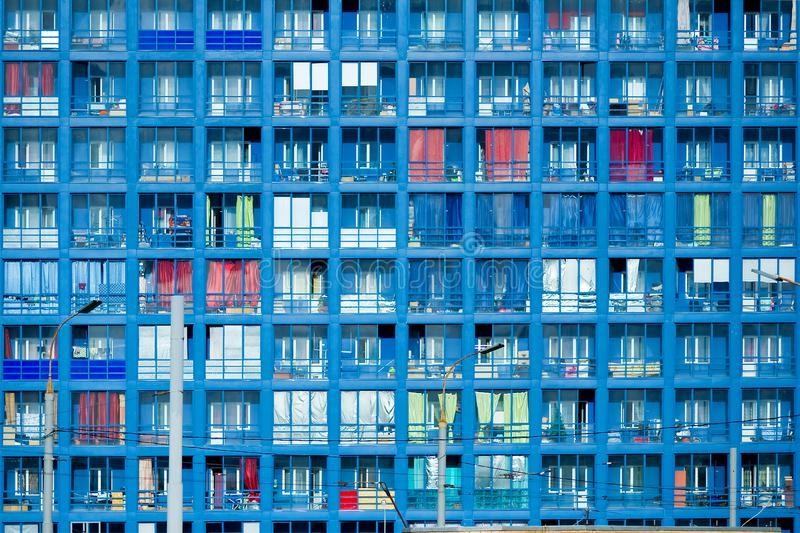 Fragment of a blue residential building with a large number of balconies and windows. Facade of a residential building in blue. Pattern of a large number of stock image