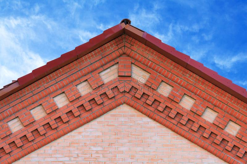 Fragment of a brick gable with decorative frieze. On a blue sky background royalty free stock photos