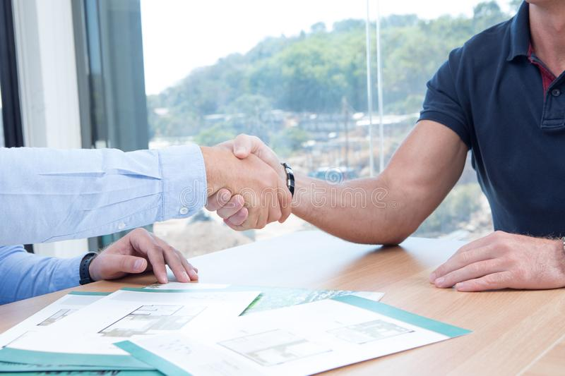 People shaking hands in office background. Fragment of business people shaking hands in office background royalty free stock photography