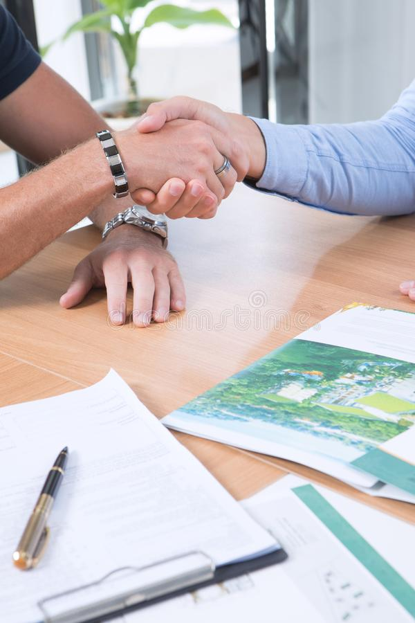 People shaking hands  in  office  background. Fragment of business people shaking hands  in  office  background royalty free stock images