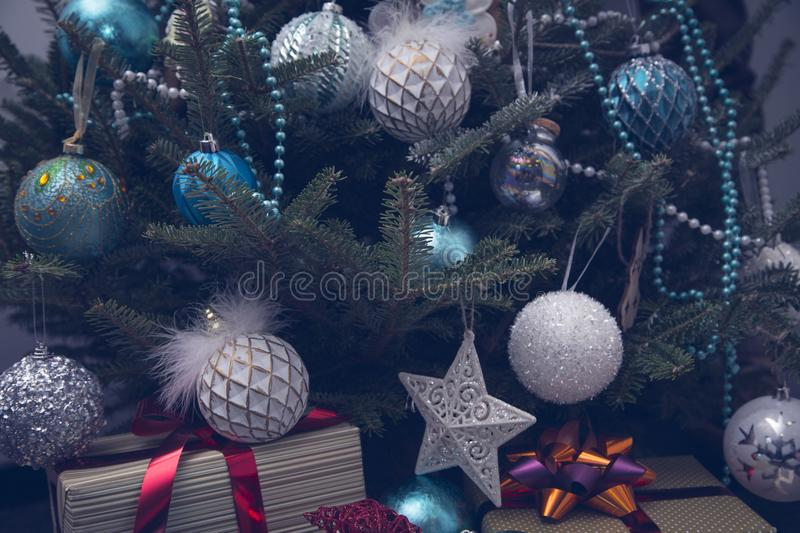 A fragment of a Christmas tree with baubles and gifts. Elegant decorations in white and blue colors hanging on a Christmas tree. A pile of beautiful gift boxes stock image