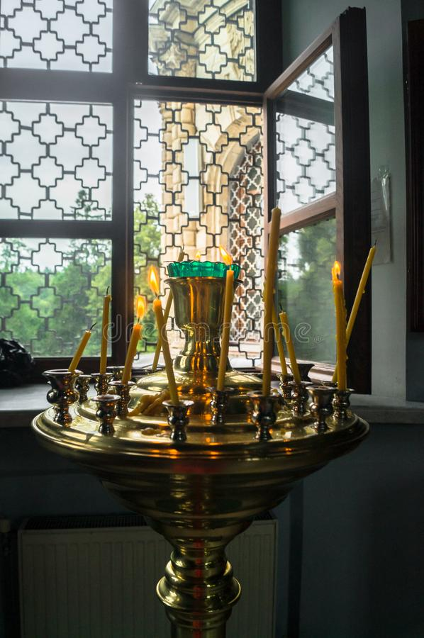 An opened latticed window and a gilt candle holder with burning and extinguished wax candles in the Orthodox Christian church. royalty free stock photos