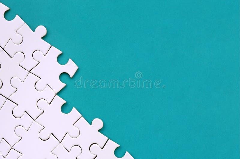 Fragment d'un puzzle denteux blanc plié sur le fond d'une surface en plastique bleue Photo de texture avec l'espace de copie pour photo stock