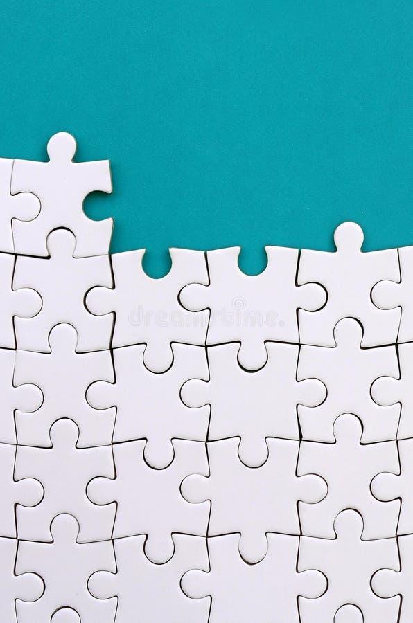 Fragment d'un puzzle denteux blanc plié sur le fond d'une surface en plastique bleue Photo de texture avec l'espace de copie pour images stock