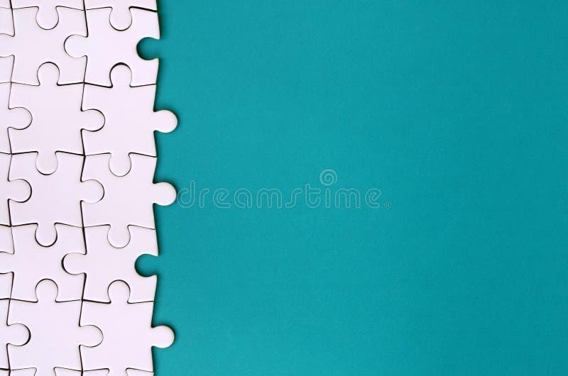 Fragment d'un puzzle denteux blanc plié sur le fond d'une surface en plastique bleue Photo de texture avec l'espace de copie pour image libre de droits