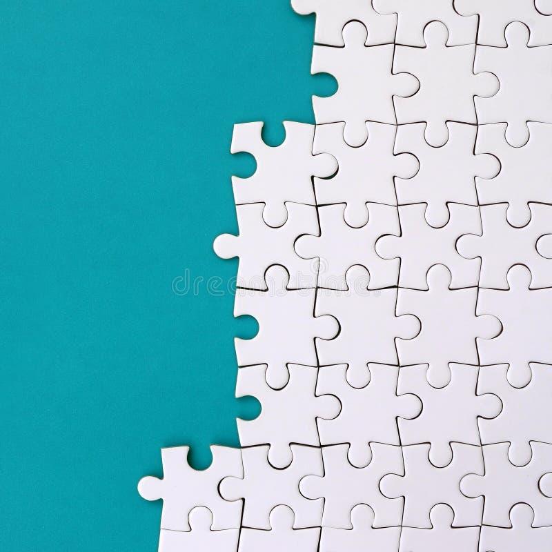 Fragment d'un puzzle denteux blanc plié sur le fond d'une surface en plastique bleue Photo de texture avec l'espace de copie pour photos stock
