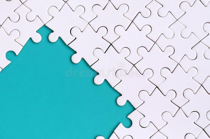 Fragment d'un puzzle denteux blanc plié sur le fond d'une surface en plastique bleue Photo de texture avec l'espace de copie pour image stock
