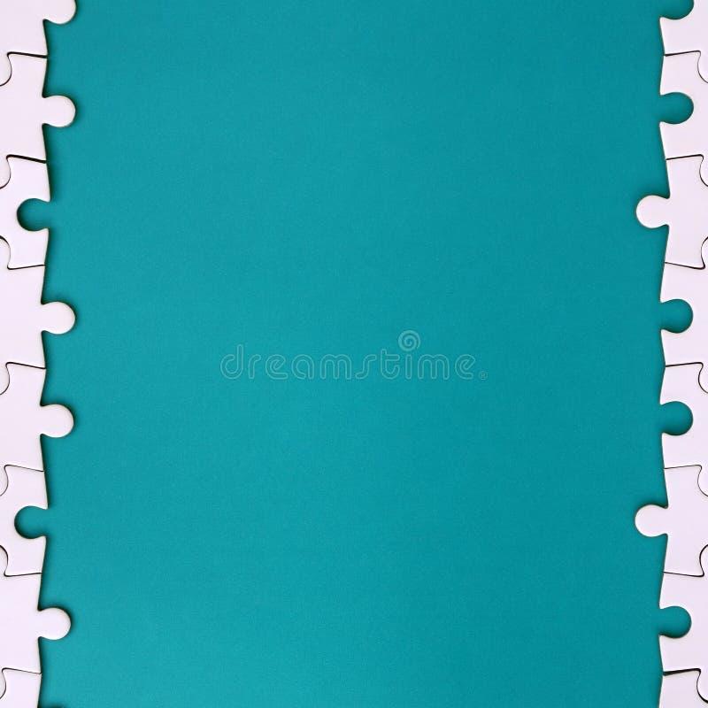 Fragment d'un puzzle denteux blanc plié sur le fond d'une surface en plastique bleue Photo de texture avec l'espace de copie pour photo libre de droits