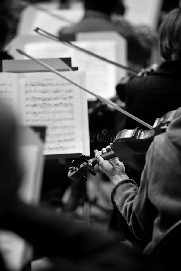 Fragment d'un violon dans les mains d'un musicien dans l'orchestre symphonique photos stock