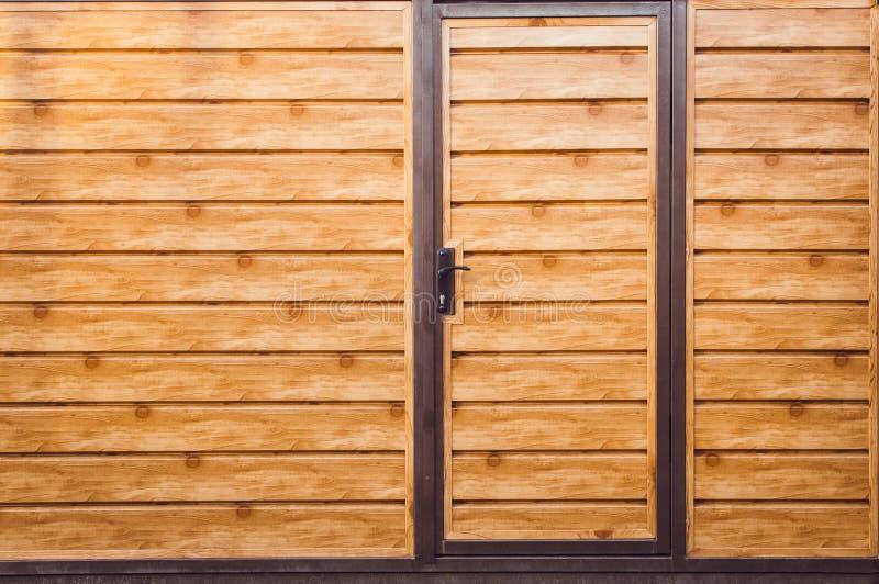 Fragment d'une barrière moderne brune en bois avec une porte d'entrée, plan rapproché Front View r photographie stock