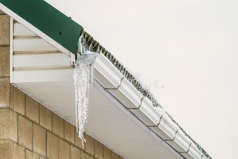 Fragment de corniche de toit avec la gouttière glaciale de glaçon de surplomb après dégel photo stock