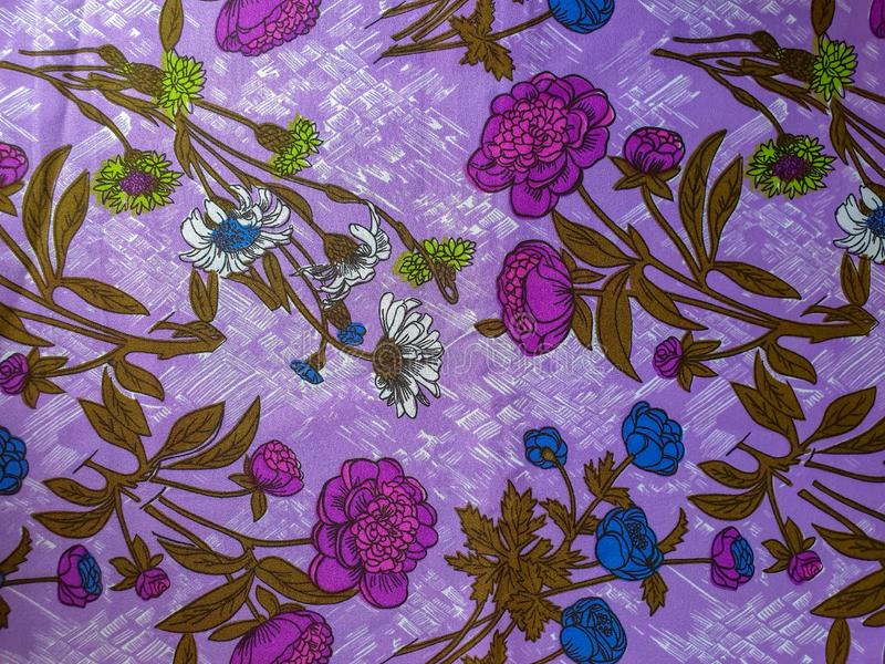 Fragment de modèle coloré de textile de cru avec l'ornement floral violet et bleu utile comme fond ou échantillon de tissu Vif et photographie stock