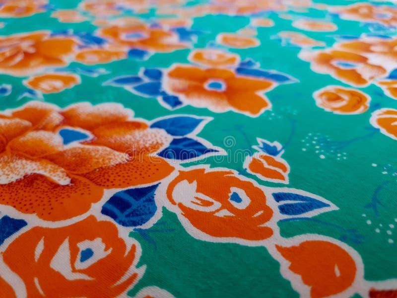Fragment de modèle coloré vert lumineux de textile de cru d'herbe avec de grandes fleurs oranges utiles comme fond ou échantillon images stock