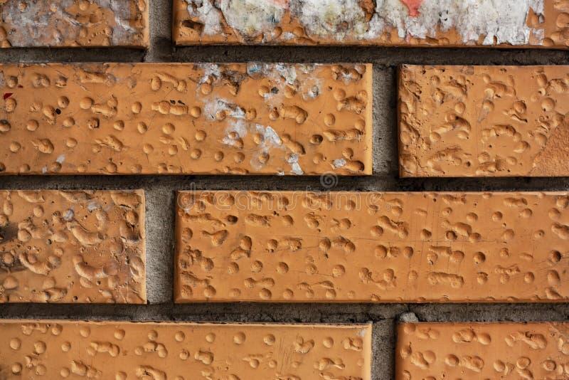 Fragment de mur de briques Vieilles briques oranges sales avec des défauts Texture grunge avec des fissures et superficielle par  photographie stock