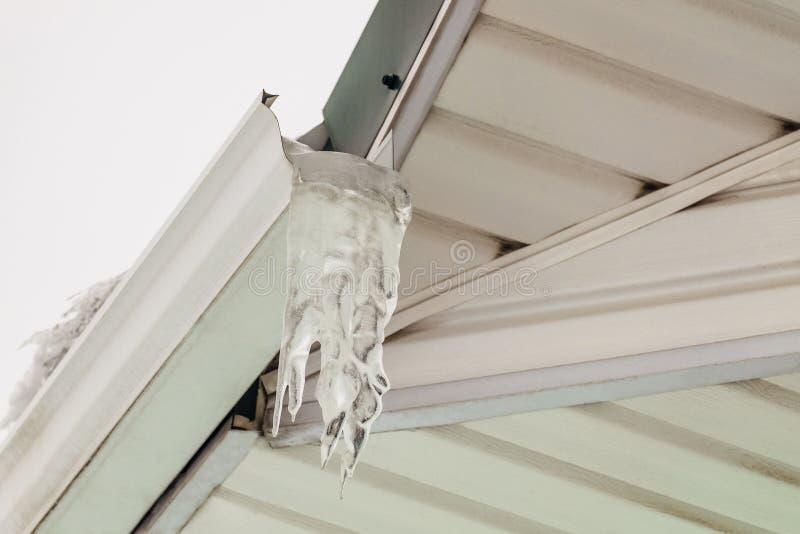 Fragment de surplomb de toit avec la gouttière glaciale de glaçon photographie stock