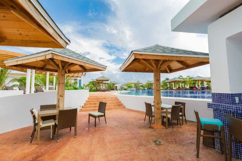 Fragment der Ansicht der bequemen Swimmingpool- und Poolbarsitzecke mit den Leuten, die, schwimmend im Hintergrund sich entspanne stockbild