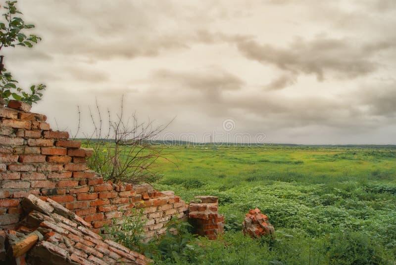 Fragment der zerstörten Wand von den landwirtschaftlichen Gebäuden auf den Gebieten unter den Wolken lizenzfreie stockbilder