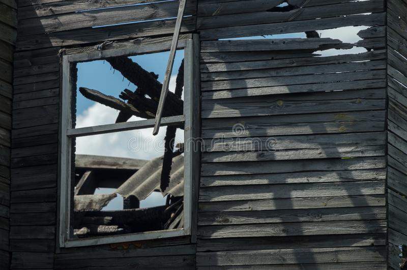Fragment of the destroyed burned wooden house wall and window. Remains of the structure. View through the window stock photo
