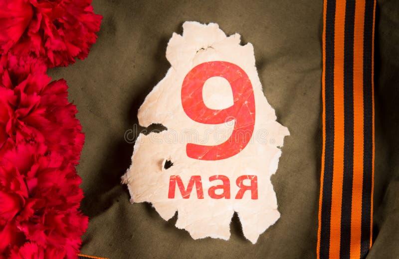 Fragment du vieux calendrier le 9 mai, un bouquet des oeillets et du ruban rouges de St George, parmi un manteau de tente photo stock