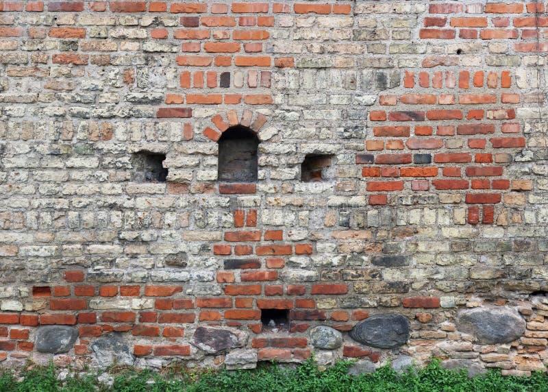 Fragment du vieux mur de forteresse de brique avec des échappatoires pour la pousse photo stock