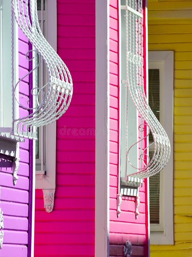 Fragment einer Mehrfarbenfassade des Hauses mit gebogenen Stangen auf den Fenstern stockbild