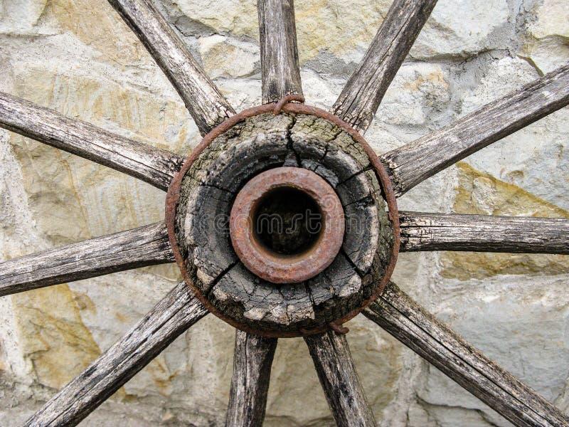 Fragment eines alten hölzernen Wagenrads gegen eine Wand des Natursteins stockfotos