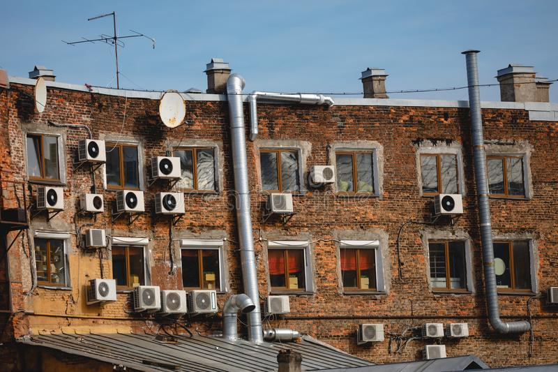 Fragment eines Backsteinhauses mit Satellitenantennen und Klimaanlagen lizenzfreies stockbild