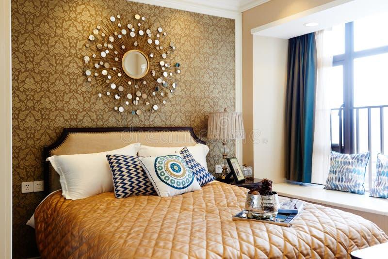 Fragment eines Betts mit weißer Kissen-, nightstand- und Wandlampe stockfotografie
