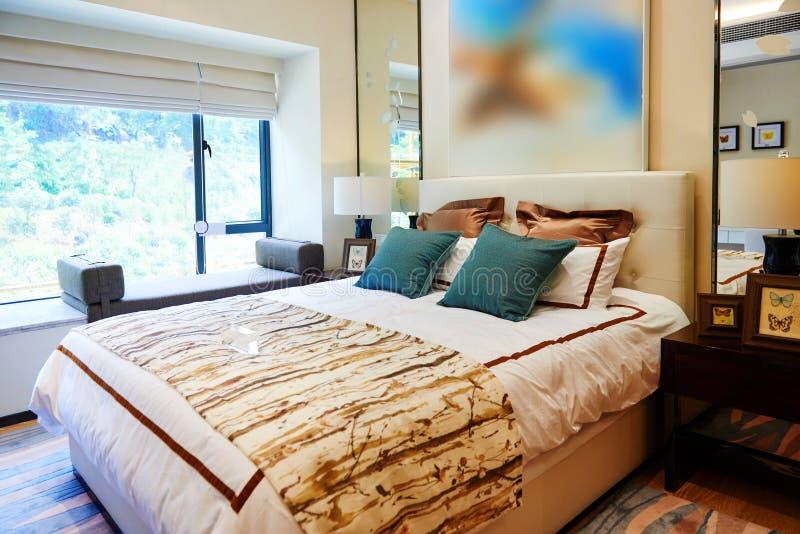 Fragment eines Betts mit weißer Kissen-, nightstand- und Wandlampe stockfoto