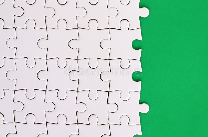 Fragment eines gefalteten weißen Puzzlen auf dem Hintergrund einer grünen Plastikoberfläche Beschaffenheitsfoto mit Kopienraum fü stockfoto