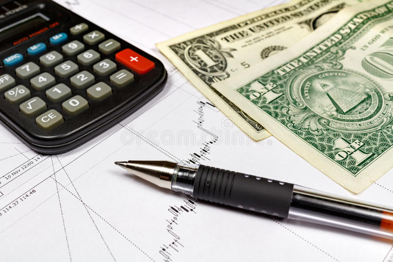 Fragment of electronic calculator with ball pen and US dollars banknotes on the background of currency growth schedule royalty free stock images