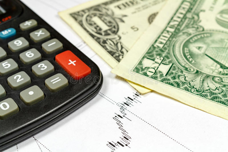 Fragment of electronic calculator and US dollars banknotes on the background of currency growth schedule stock photography