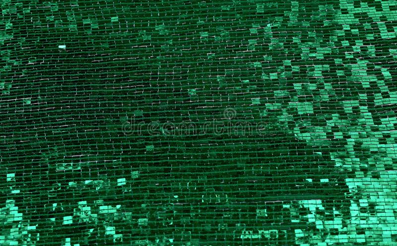Fragment of fabric embroidered with green square sequins. Full frame stock photo