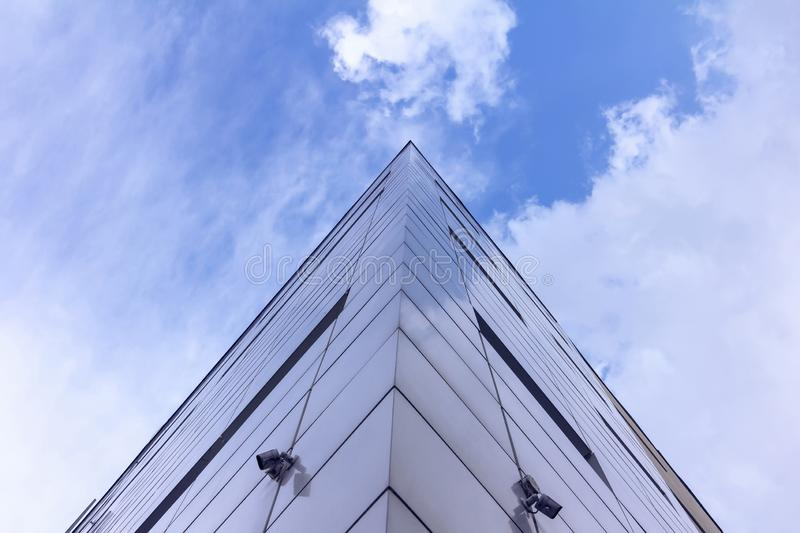 Fragment of the facade of abstract modern commercial architecture, the corner of the walls under a blue cloudy sky stock photos