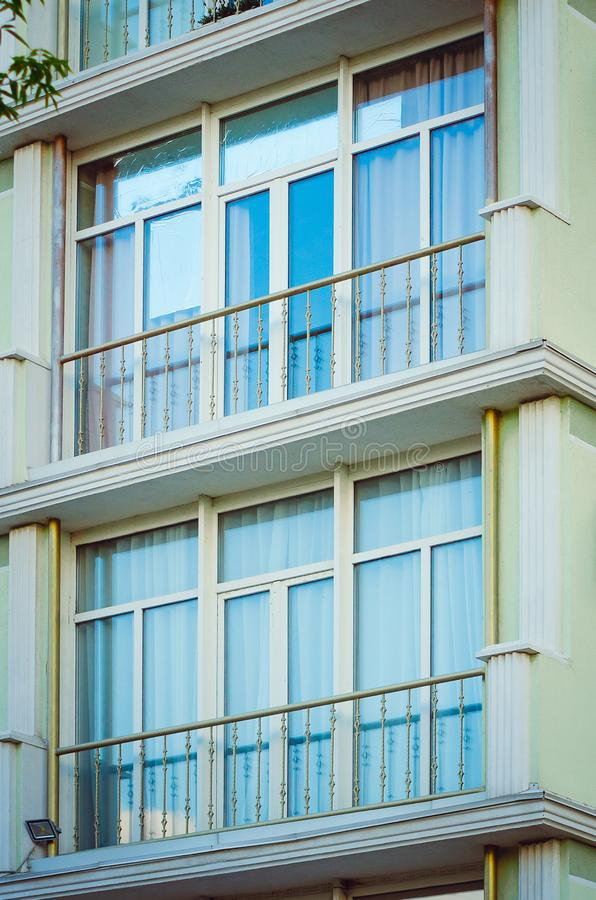 Fragment of the facade of a modern apartment house with a window and a balcony stock photos