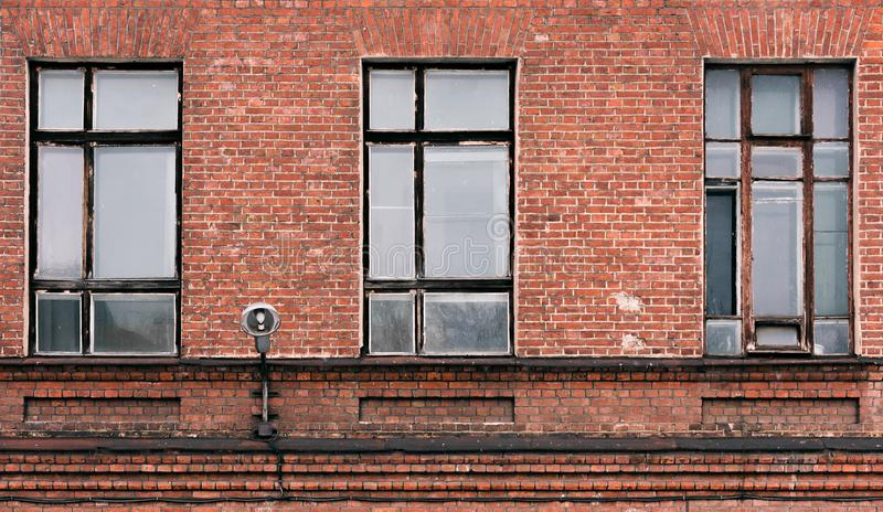 Fragment of the facade of an old brick building. High Windows and textural materials royalty free stock photo