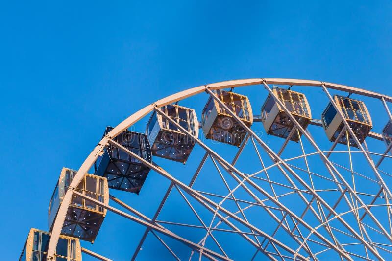 Fragment of ferris wheel at sunset. Full metal ferris wheel gondolas at sunset against deep blue skies stock images