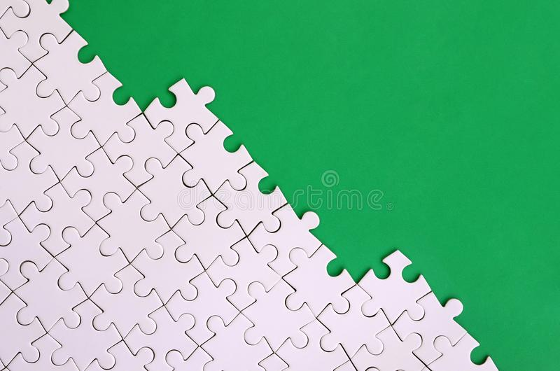 Fragment of a folded white jigsaw puzzle on the background of a green plastic surface. Texture photo with copy space for text.  stock photos