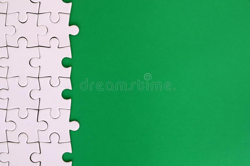 Fragment of a folded white jigsaw puzzle on the background of a green plastic surface. Texture photo with copy space for text.  stock photography