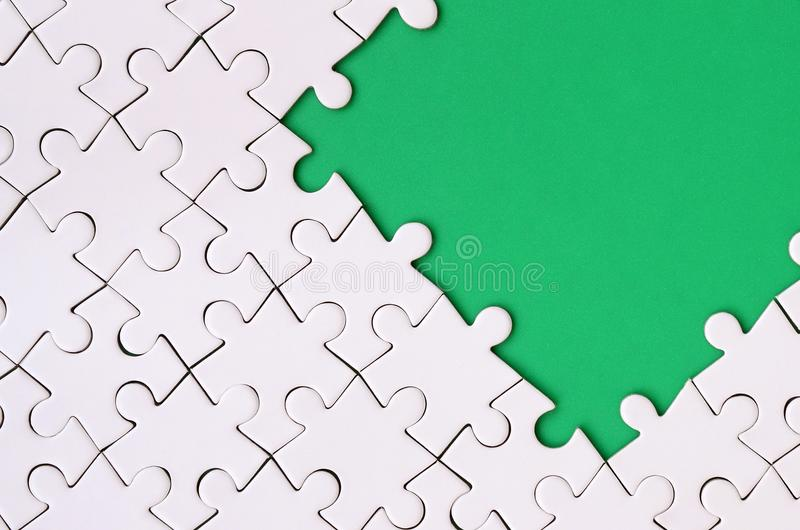 Fragment of a folded white jigsaw puzzle on the background of a green plastic surface. Texture photo with copy space for text.  royalty free stock photos