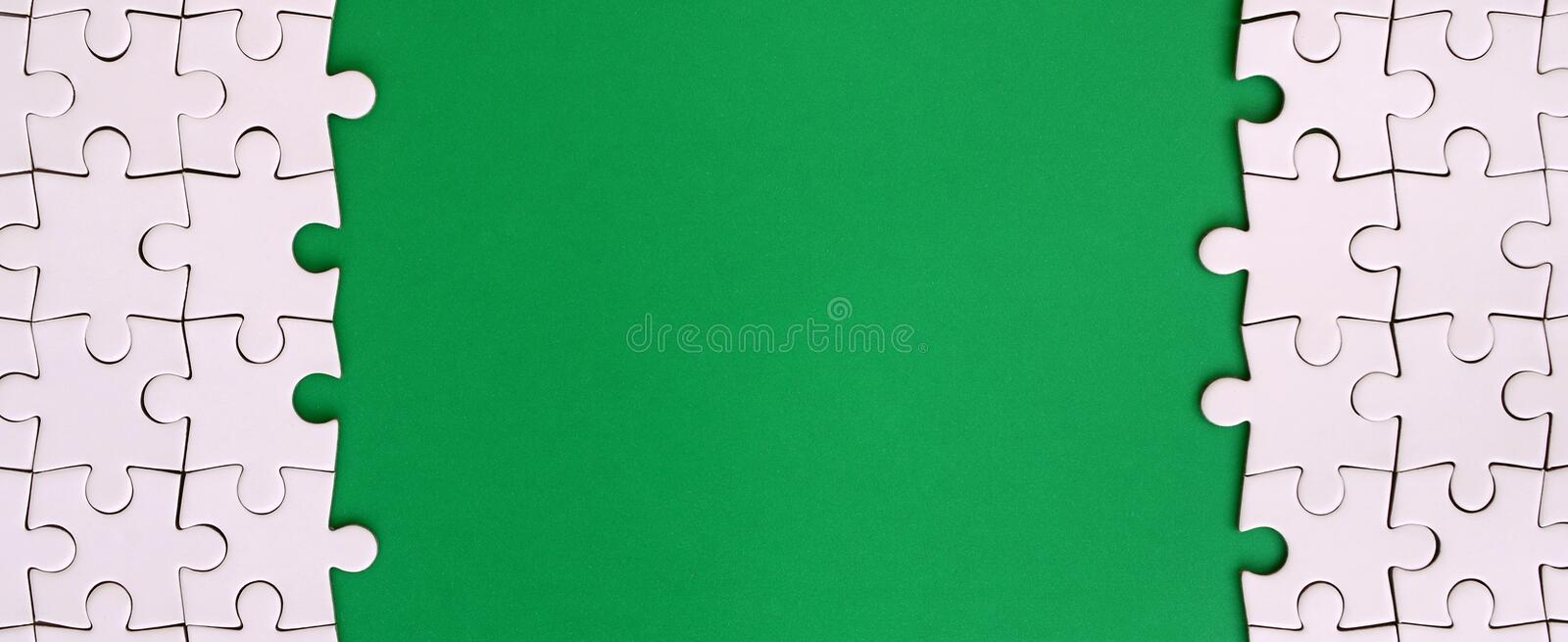Fragment of a folded white jigsaw puzzle on the background of a green plastic surface. Texture photo with copy space for text.  stock images