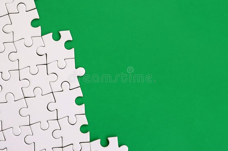 Fragment of a folded white jigsaw puzzle on the background of a green plastic surface. Texture photo with copy space for text.  royalty free stock photography