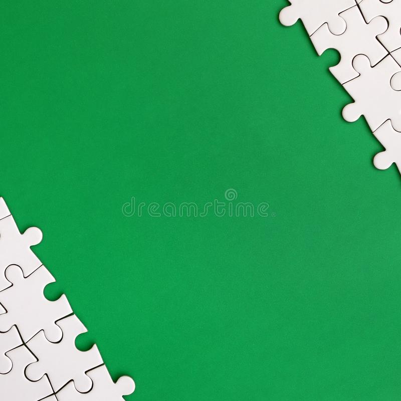 Fragment of a folded white jigsaw puzzle on the background of a green plastic surface. Texture photo with copy space for text.  royalty free illustration